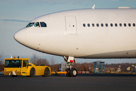 tow tractor: Detail on huge white airplane during towing.