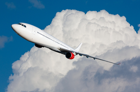 aeroplanes: Huge white plane flying with clouds in background Stock Photo