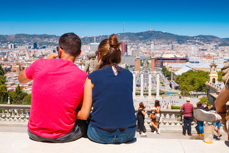 montjuic: Barcelona, Spain - August 10, 2017:  Young couple looking from Montjuic to Plaza de Espana including the four columns and the venetian towers in Barcelona, Spain