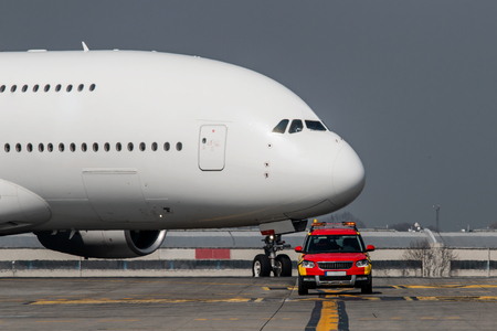 Huge white airplane follow car on the taxiway