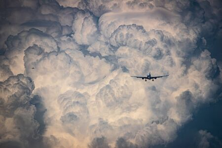 Two airplanes approaching for landing with beatiful stormy clouds background
