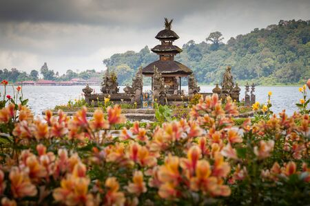 Beautiful Balinese Ulun Danau temple on lake Beratan in cloudly day in extinct volcano crater in Bali, Indonesia.