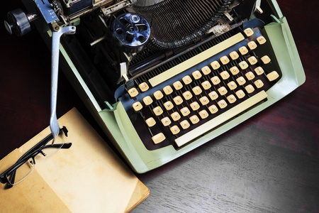 Old typewriter and old book on the table. Stock Photo