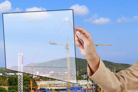 Hand of Secretary show a grow up arrow with construction site background photo