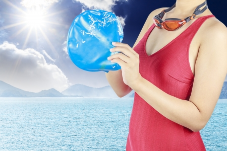 Young woman with red swimsuit and with a swimming cap  on  sea background Stock Photo - 14566992