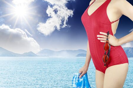 Young woman with red swimsuit and with a swimming cap  on  sea background photo