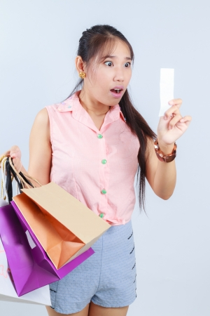 young woman shocking after checking over the receipt in her hands and spending too much Stock Photo