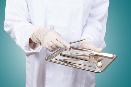 doctors tools: Closeup of dentist hand taking mirror from on of dental tools. Stock Photo