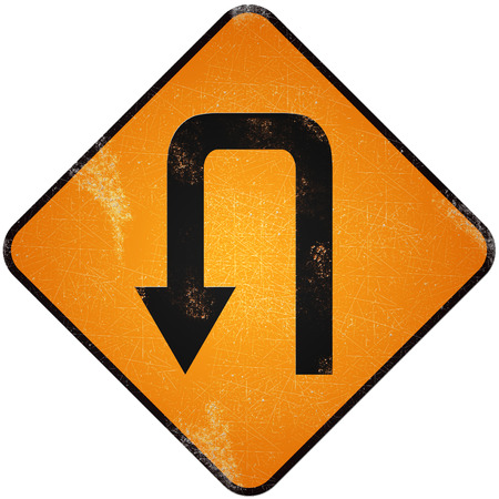 U turn road sign. Damaged yellow metallic road sign with U turn symbol.