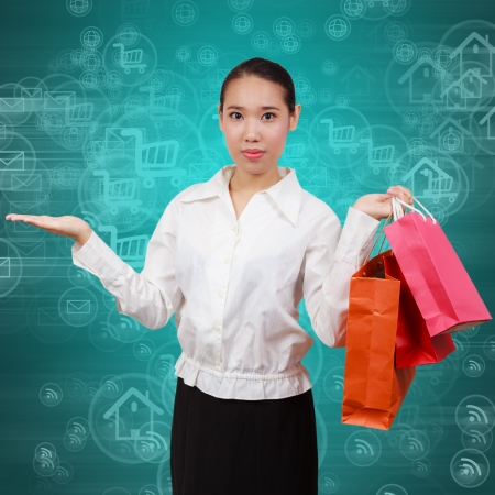 Shopping women show empty hands and hold shopping bags. On background with symbols network and Internet. Concept Communication and borderless business spending. photo