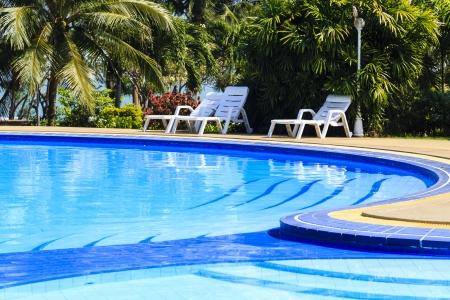 白いサンデッキと豪華なスイミング プールはトロピカル ガーデンのクローズ アップ