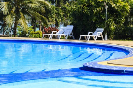 deck: luxury swimming pool with sundeck white close up in tropical garden  Stock Photo