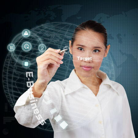 Business woman writing business target on virtual screen. Stock Photo - 26321935