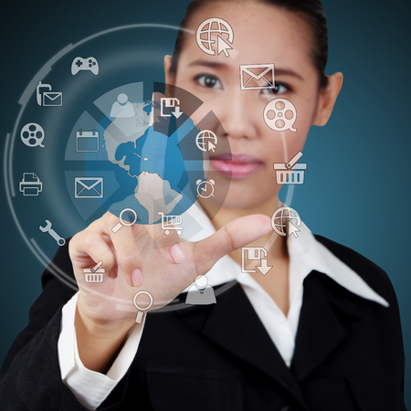 Business woman touching the globe and icon application on virtual screen. Concept of online business. photo