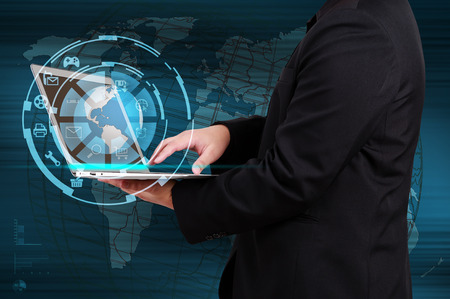 Businessman holding a laptop with globe and icon application on virtual screen photo