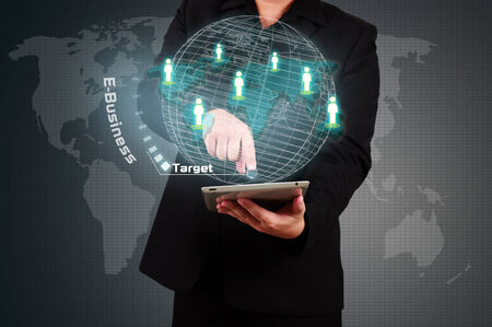 Businessman holding tablet and touching a target on virtual screen photo