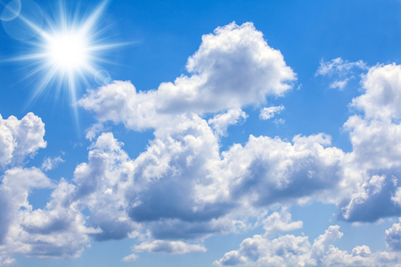 A blue sky with bright sun and clouds.