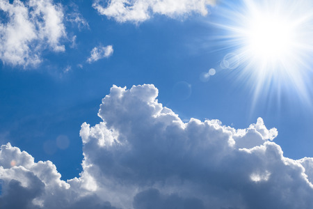 Blue sky with sun and bright puffy clouds.