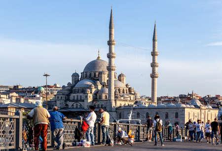 Istanbul / Turkey - 07.01.2015: New Mosque at the back side of the Fishermen on Galata Bridge. Eminonu, Istanbul, Turkey.