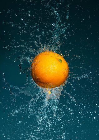 Ripe and juicy orange in water splashes