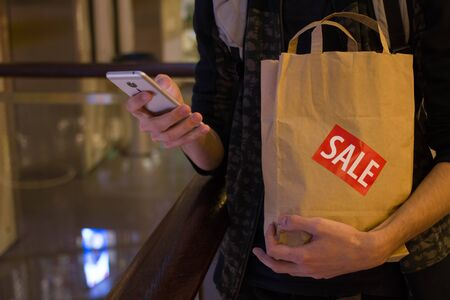 Man hold brown paper bag with SALE sticker on it in one hand and use smartphone with another Close up HD