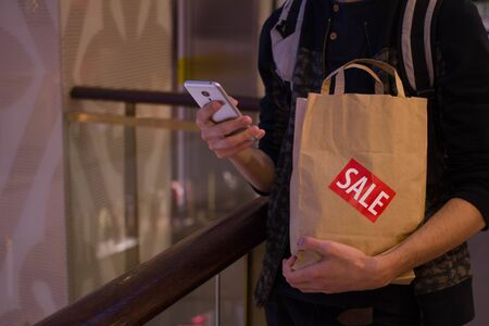 brown paper bag: Man hold brown paper bag with SALE sticker on it in one hand and use smartphone with another Close up HD
