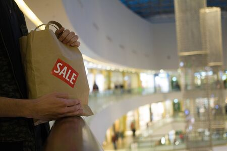 brown paper bag: Man hold brown paper bag with SALE sticker on it in one hand Close up HD