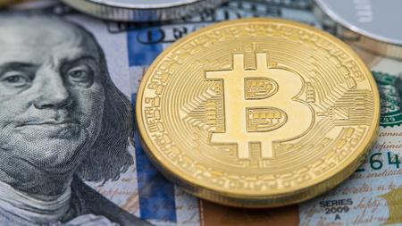 Physical metal golden Bitcoin currency over 100 dollar bill United States. Worldwide virtual internet money with USA banknotes. Digital coin cyberspace, cryptocurrency gold BTC. Online payment