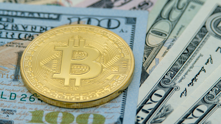 Physical metal golden Bitcoin currency over dollars bills of United States. Worldwide virtual internet money with USA banknotes. Digital coin cyberspace, cryptocurrency gold BTC. Online payment
