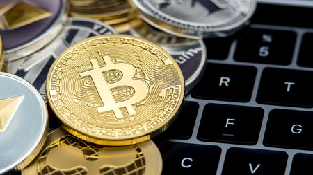 Physical metal golden Bitcoin currency on notebook computer keyboard. Worldwide virtual internet money. Digital coin cyberspace, cryptocurrency gold BTC. Good investment future online payment