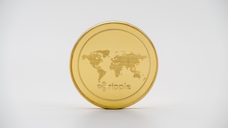 Physical metal golden Ripplecoin currency on white background. New worldwide virtual internet money. Digital Ripple coin cyberspace, cryptocurrency XRP. Good investment future online payment Stock Photo