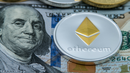 Physical metal silver Ethereum currency over 100 dollar bill of United States. Worldwide virtual internet money with USA banknotes. Digital coin cyberspace, cryptocurrency ETH. Online payment