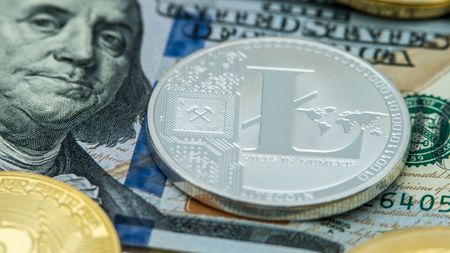 Physical metal silver Litecoin currency over dollar bill of United States. Worldwide virtual internet money. USA banknotes. Digital Lite coin cyberspace, cryptocurrency LTC. Online payment