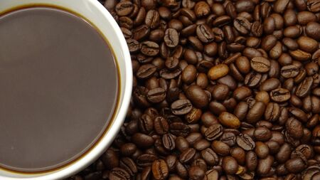 A cup of black coffee over roasted coffee beans