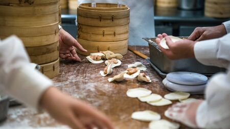 Taiwanese team of chefs cooking traditional food. Asian chef making fresh dumplings in the restaurant of Taiwan. Men hands cook and prepairing dough of dumpling.