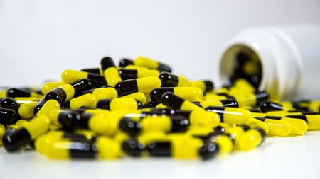Close up on a bottle of prescription drugs falling out. Black and yellow pills and tablets medicine isolated on white background. A lot of medication, painkillers and drug abuse concept. Reklamní fotografie