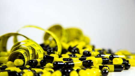 Black and yellow pills with measuring tape on white background to represent the diet pill industry. Healthy eating, health care, food supplements and weight loss concept. Prescription drugs isolated.