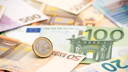 Closeup of a coin one euro with banknotes of different values. Cash money background. Real hundred euros. Good earnings. Issuing salary. Credit percent. Successful business