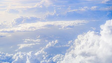 The beautiful cloudscape with clear blue sky. Panorama above white clouds as seen through window of an aircraft. A view from airplane window Reklamní fotografie - 125072473