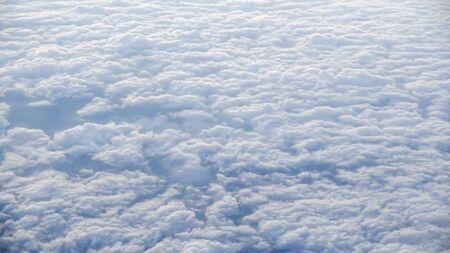 The beautiful cloudscape with clear blue sky. Panorama above white clouds as seen through window of an aircraft. A view from airplane window Reklamní fotografie - 125072479