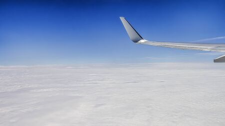 Close up of window with airplane wing. Beautiful cloudscape with clear blue sky. Panorama above white clouds as seen through window of an aircraft. Traveling concept.