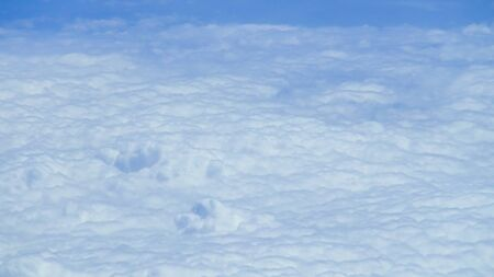 The beautiful cloudscape with clear blue sky. Panorama above white clouds as seen through window of an aircraft. A view from airplane window Reklamní fotografie - 125072484