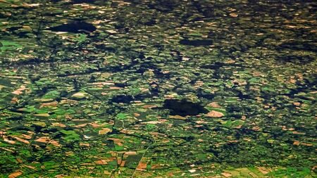 Beautiful view of European countryside from above, as seen through airplane window. Passenger POV traveling by air. Flight trip with green field. Reklamní fotografie - 125072430