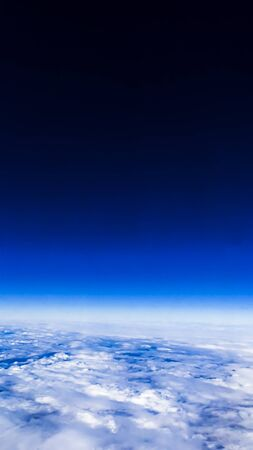 Wonderful view of cloudscape with clear blue sky from above. Beautiful panorama above white clouds as seen through window of an aircraft. A view from airplane.