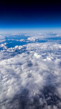 Wonderful view of cloudscape with clear blue sky from above. Beautiful panorama above white clouds as seen through window of an aircraft. A view from airplane. Reklamní fotografie - 125072432