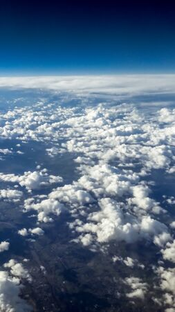 The beautiful cloudscape with clear blue sky. Panorama above white clouds as seen through window of an aircraft. A view from airplane window Reklamní fotografie - 125072435