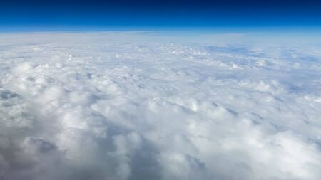 The beautiful cloudscape with clear blue sky. Panorama above white clouds as seen through window of an aircraft. A view from airplane window Reklamní fotografie - 125072434