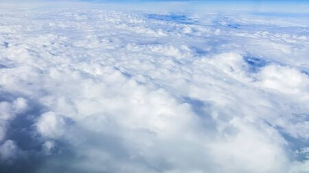 The beautiful cloudscape with clear blue sky. Panorama above white clouds as seen through window of an aircraft. A view from airplane window Reklamní fotografie - 125072436