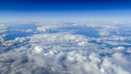 The beautiful cloudscape with clear blue sky. Panorama above white clouds as seen through window of an aircraft. A view from airplane window Reklamní fotografie - 125072439