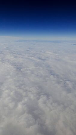 The beautiful cloudscape with clear blue sky. Panorama above white clouds as seen through window of an aircraft. A view from airplane window Reklamní fotografie - 125072441